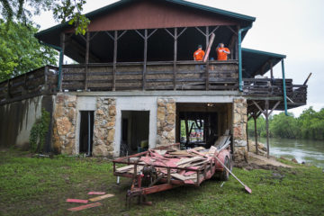 Volunteers discard flood-damaged boards from Phillip Wiggs' riverside home.