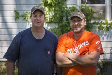 Homeowner Scott Smith and neighbor Jason Latham bond while working together to clean up Scott's home from flood damage.