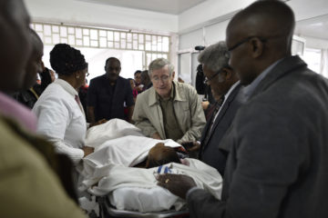 Ed Morrow, director of World Medical Mission, comforts one of the survivors during transport from Tanzania.