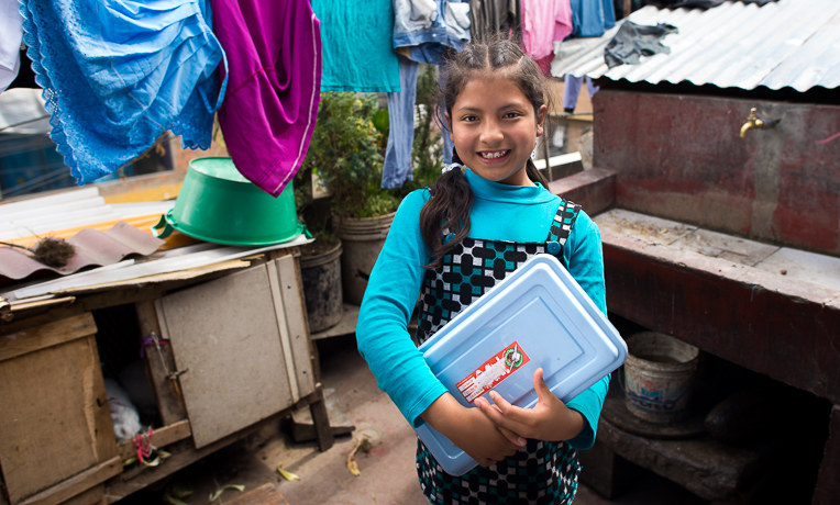 Paola proudly shows off her shoebox gift outside of her home.