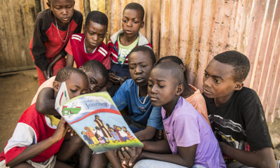 Innocent shares a story from The Greatest Journey workbook with other boys in his neighborhood.