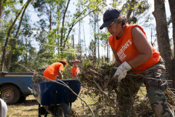 Elvira Martorello clears fallen tree limbs from David Bailey's yard during her first deployment as a Samaritan's Purse disaster relief volunteer.