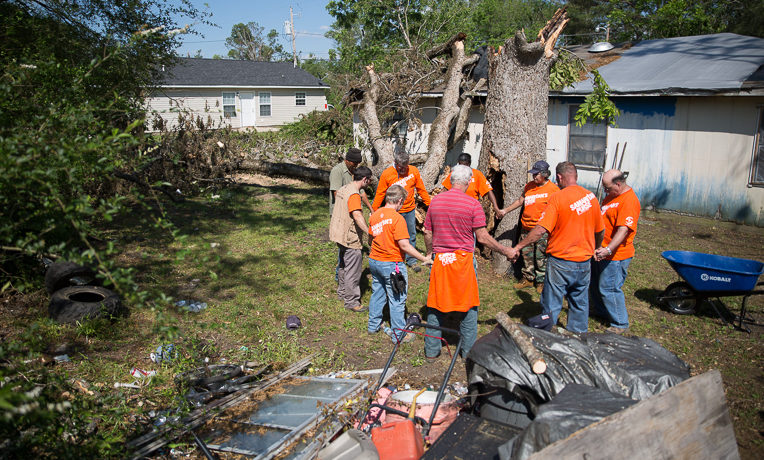 Volunteers pray in David Bailey's yard where a tornado caused roof damage. David is one of 110 people in Durant, Mississippi, who made a profession of faith in Jesus Christ during the past two months.