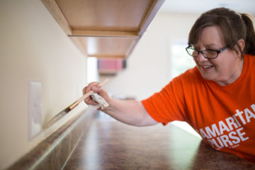 Erika Zajdel, a youth leader from First Evangelical Free Church of McKeesport, Pennsylvania, touches up the paint in James Horne's new kitchen.