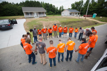 Samaritan's Purse staff and volunteers pray with the Horne family outside James' new home.