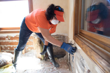 Retired firefighter Amy Jo Walter from Orangeville, Illinois, tears out waterlogged walls for a Wisconsin homeowner.