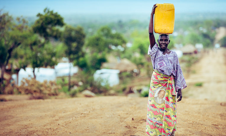 A South Sudanese refugee balances her water jug. The skirt she's wearing features the image of John Garang, a South Sudanese leader who laid the foundation for nation's independence and died in 2005.
