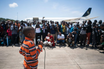 Wilson speaks to the gathered crowd at the airport back home in Tanzania.
