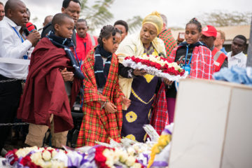 Wilson, Doreen, and Sadhia lay wreaths in front of a newly dedicated monument to the 32 students, two teachers, and driver who died in the May 6 bush crash.