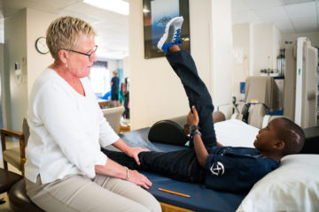Wilson works with physical therapist Mona Hanson at Mercy Medical Center.