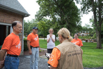 Homeowner Sonya Green receives a Bible signed by the volunteers who worked on her home.