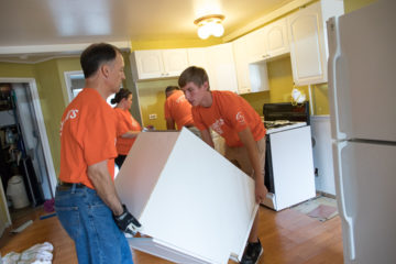 Volunteers Dale Eggert and Will Ford remove a cabinet in order to work on the water-logged wall.