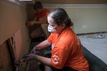 Carol Anno removes waterlogged dry wall.