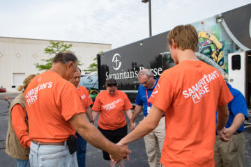 Samaritan's Purse volunteers and Billy Graham Rapid Response Team chaplains pray together before setting out to work and minister.