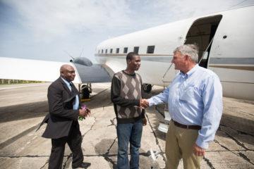 Francois Joseph and Pastor Nigel Henry (at left) greet Franklin Graham in Barbuda.