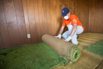 Jenny Koselak removes damaged carpet from a home in Rockport.