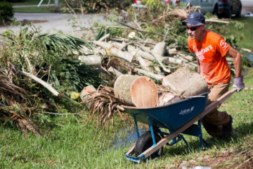 A Samaritan's Purse volunteer works hard clearing trees and debris in Marta's yard.