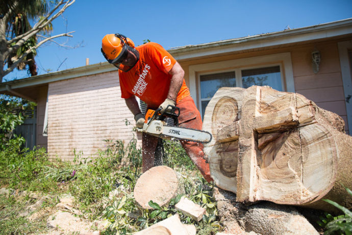 Site Team Leader Tommy Smith carved a cross into the stump of the Poinciana tree in Marta Moriarty's yard
