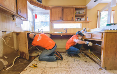 Volunteers rip out waterlogged cabinets in the Sherman's home.