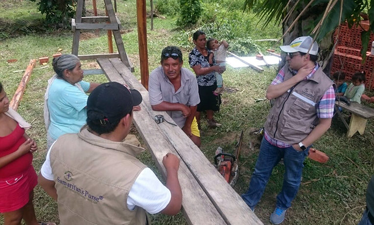 Adolfo talks with Samaritan's Purse personnel at the construction site for Puente Caimanes' poultry dressing center, which will help beneficiaries prepare their products for market.