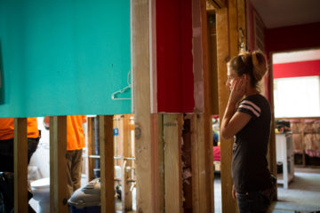 Sara Tallman stands in her hurricane-damaged home in Santa Fe, Texas. To the left, our volunteers are working.