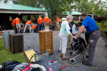 A Billy Graham Rapid Response Team chaplain prays with Renee as Samaritan's Purse volunteers continue to clean up.