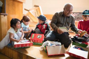 Evgeniy Varode helps children in the neighboring village of Seredne discover what is inside their shoeboxes.