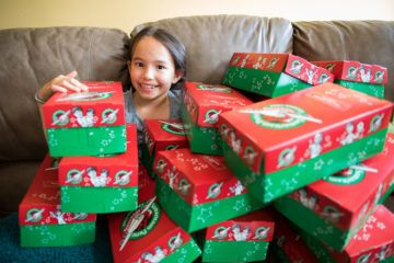 Lily is surrounded by shoebox gifts which combine two of her favorite things: helping others and organizing.