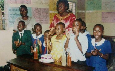 Hilda, at center in yellow, celebrates her 12th birthday in school in Uganda.