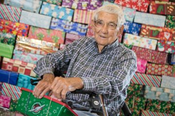 Ira holds the 100th shoebox in front of a colorful wall display of the 99 others he's packed.
