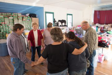 Members of Brushed Up Ministries pause to pray after setting up for the packing party on Saturday afternoon.