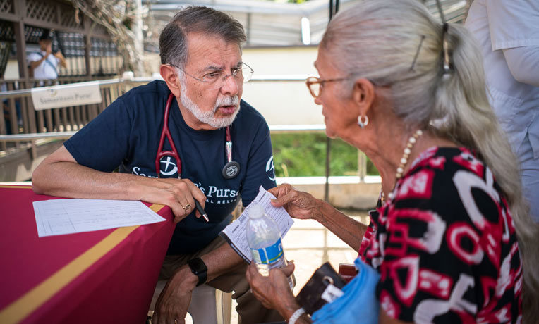 Dr. Carlos de la Garza consults with a patient in rural Puerto Rico.