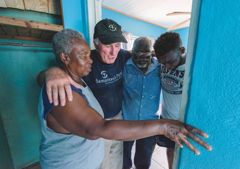 Ray Helm of Samaritan's Purse prays with Charles and Netta Williams and their grandson.