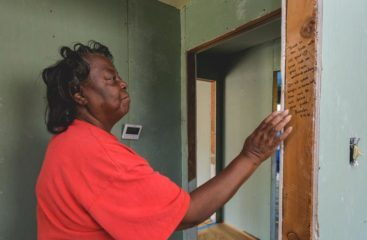 Mary Hooey contemplates Proverbs 3:5-6, written by a volunteer on the frame of her doorway.