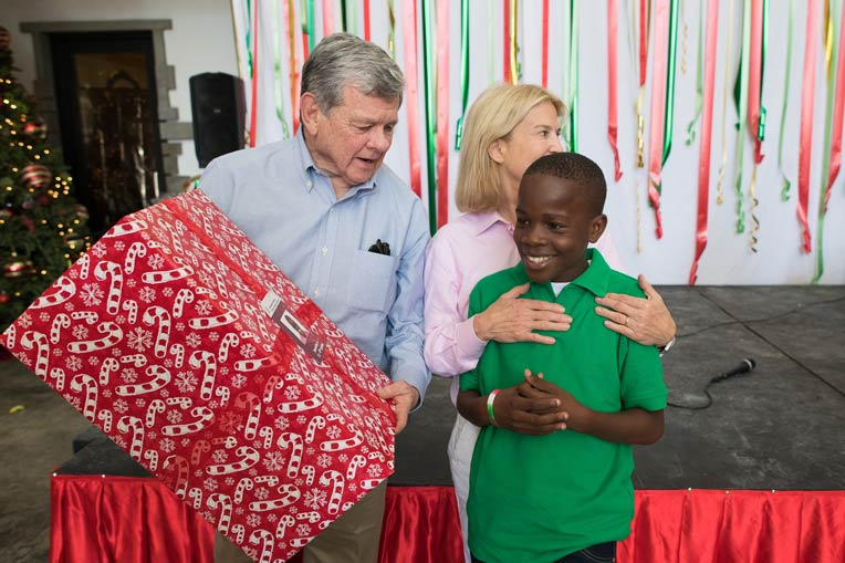 John and Greta give gifts to children