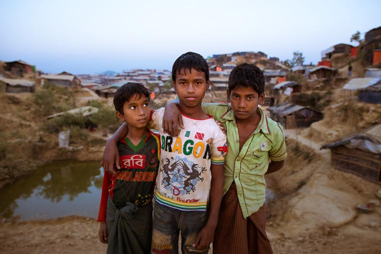 Three friends stand together in a Rohingya refugee camp.