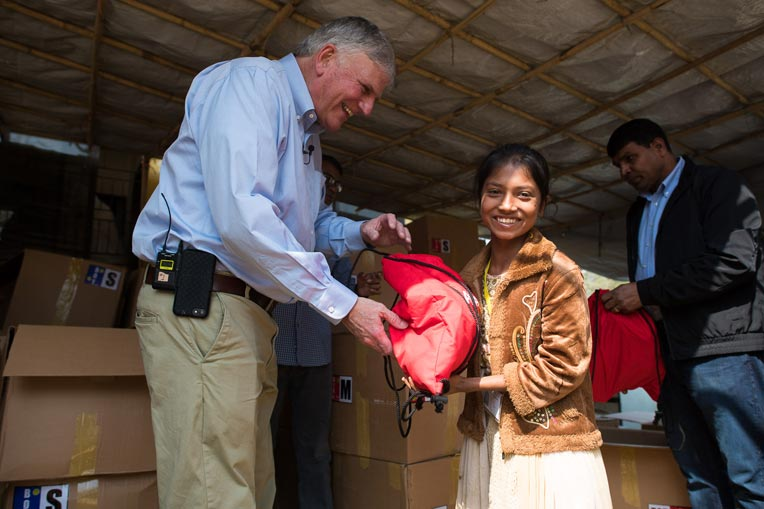 Franklin Graham gives a young Rohingya girl a backpack bag filled with special gifts from Samaritan's Purse.