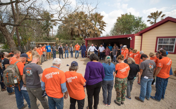 Volunteers and staff pray for the Escamilla family during the dedication.