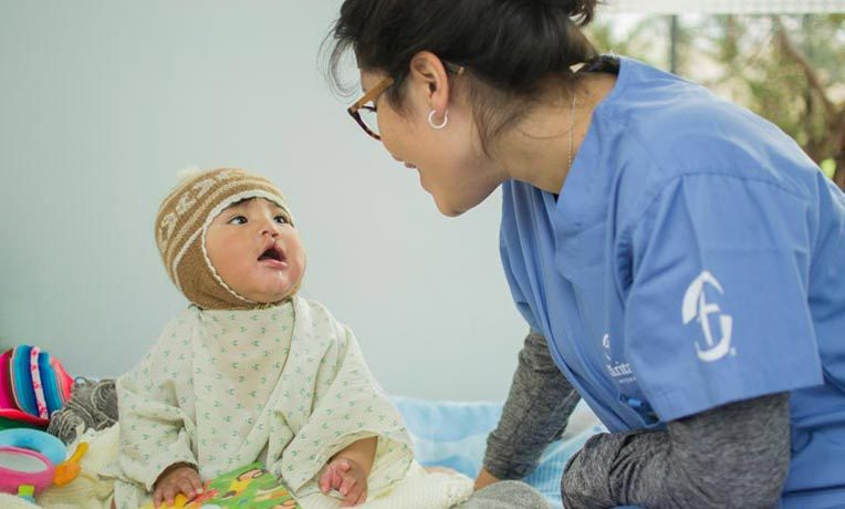 Andrea talks with Jhoel before his surgery. A university student, Andrea served as a language interpreter for the medical team and families. Jhoel's hospital bed is filled with toys and a book about Jesus.