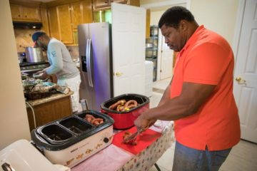 George Dorsey and his son, George III, prepare sausages, gumbo, and brisket to celebrate with Samaritan's Purse staff and volunteers.