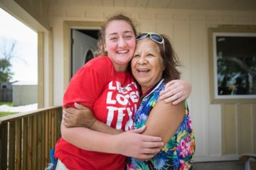 Homeowner Olga Chapa and Liberty University student Leah Andrews share a moment of laughter outside of Olga's home.