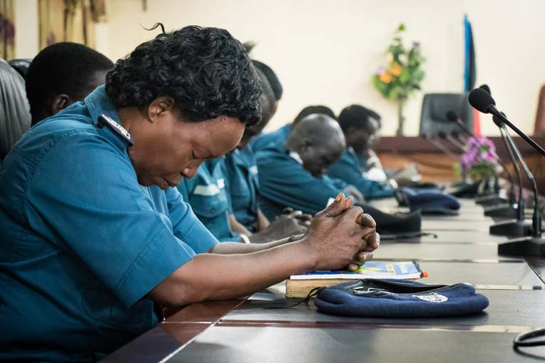 """A Republic of South Sudan police officer prays before the """"Leading Using Biblical Principles"""" workshop gets started in Juba, South Sudan."""
