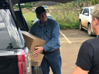 Franklin Graham unloads boxes of facemasks and Tyvek suits to give to a local community center in Hanalei, which will distribute them to families in need.