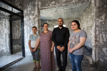 Diana (second from left) and her three children stand in their home, which was burned by ISIS. Atheer, the family's eldest son, stands to the right of his mother.
