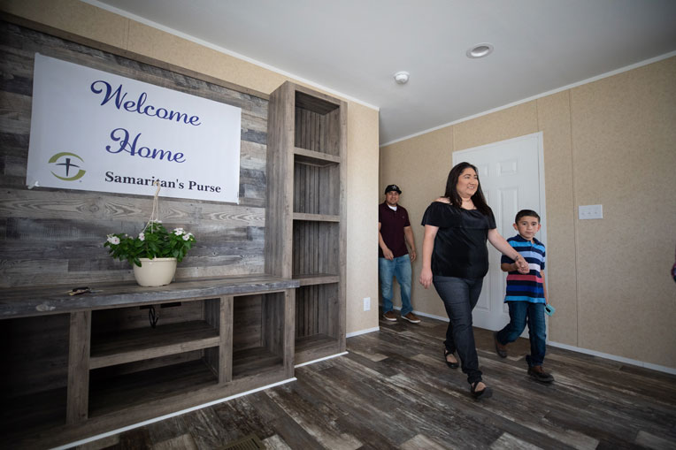 Christina Rodriguez and Jose Reyes and their children walk into their new home for the first time.