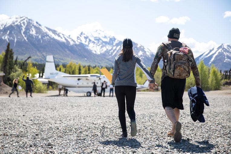 military couple walks to airplane at Samaritan Lodge Alaska