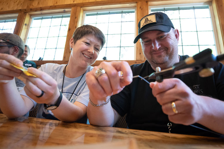 Retired Army Sergeant Shawn and Laura Riggs tie a fishing fly together.