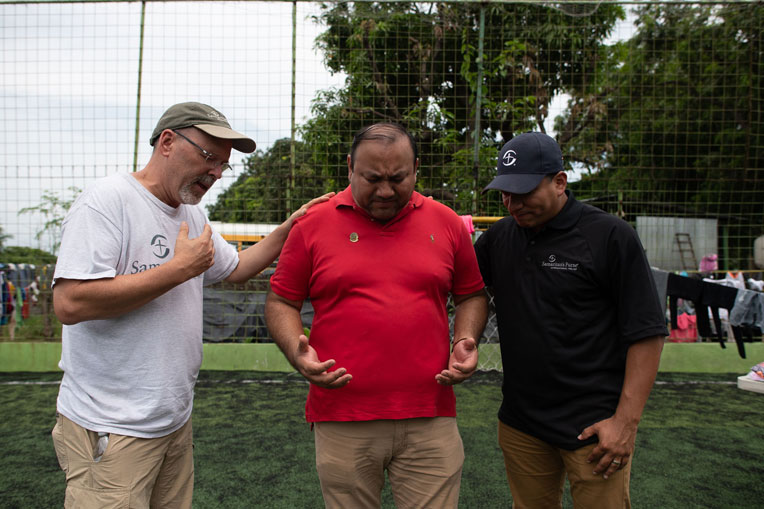 Samaritan's Purse staff pray with a local pastor in Guatemala