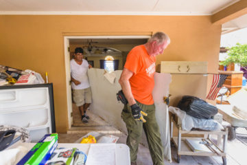 Lupe Aguirre and Team Leader Mike Parker remove a piece of ruined sheetrock.