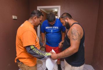 Samaritan's Purse volunteers pray with homeowner Julian Quintana Jr. before beginning work on his home.